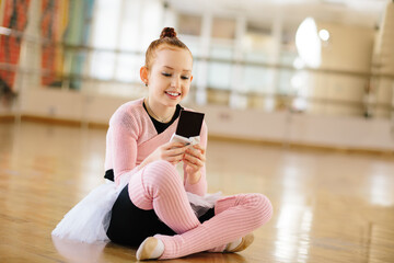 Girl ballerina eating chocolate in ballet class