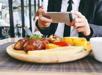 Businessman hand using smartphone to take photo of rib steak on wooden tray at restaurant.