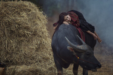 Woman farmer sleeping on the buffalo lonely.