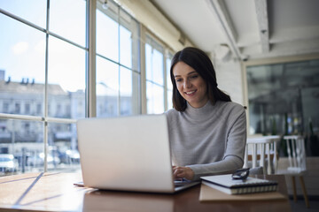 Smiling attractive female freelancer doing remote job using laptop computer connected to wireless internet in office, professional administrative manager checking online business report documentation.