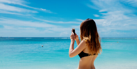 Young woman making a landcape photo with her phone. Photographing beautiful blue sea and the sky.