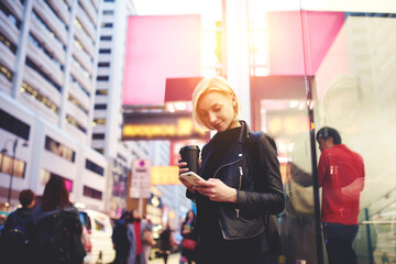 Talented female travel blogger typing text of publication about Chinese business center posting multimedia files in social network sharing impressions about Asian town using free wireless internet