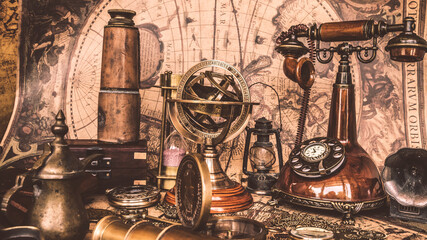 Ancient binoculars, telescope, compass and telephone on old world map.