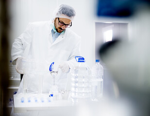 Lab technician working in a water production laboratory. Adding required components.