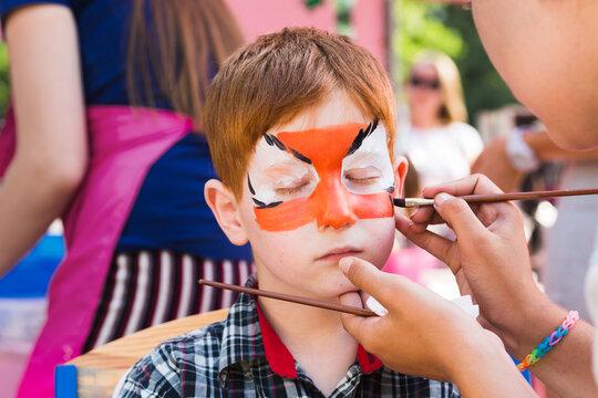 Child boy face painting, making tiger eyes process