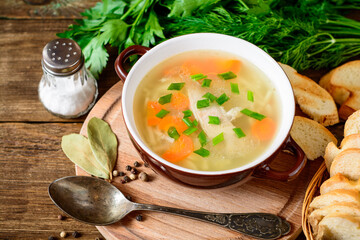 Homemade chicken soup with noodles and vegetables in ceramic bowl on wooden table.