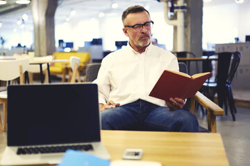 Experienced businessman dressed in stylish clothes reading favorite book during work break in office of his corporation while installing new software on laptop with mock up screen connected to wifi
