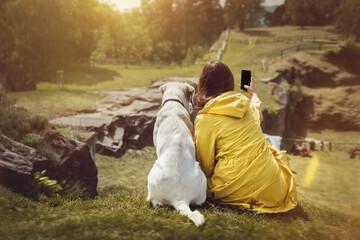 Junge Frau und schöber labrador retriever hund sitzen nebeneinander auf einem sonnigen Hügel und machen ein selfie
