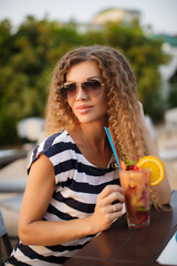 A beautiful, young woman, a brunette with long curly hair, dressed in a white dress with blue stripes,a sweet smile, wearing sunglasses,spending time in a summer cafe with a glass of fruit cocktail
