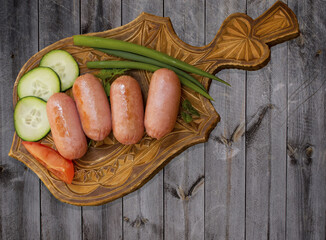 Breakfast of fried mini sausages with vegetables and a background of grey wooden table vintage top view