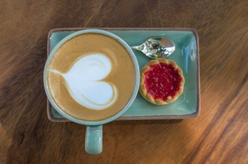 coffee cup with heart shape with strawberry biscuit on blue plate
