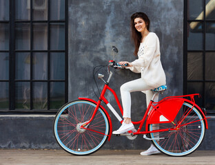 Streetstyle. Beautiful brunette girl in trendy, white outfit posing with a trendy vintage red bicycle outdoors.