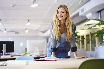 Cheerful blonde young female student of IT school preparing for quiz reading notes and information for copybook feeling confident before testing begins standing in university computer classroom