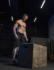 Muscular White Caucasian man about to start a box jump in a dark grungy gym wearing shorts and showing muscular body and six pack abs