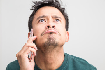 Mustache beard asian man feeling upset while talking on phone