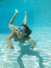 femme avec des lunettes de plongée sous l'eau dans une piscine