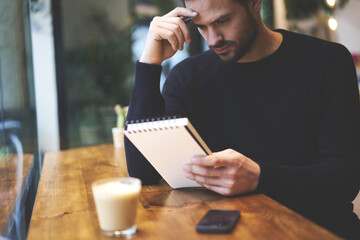 Cropped image thoughtful bearded young businessman creates startup project idea using notebook while working in contemporary coworking interior. Pensive student  studying in coffee shop indoors