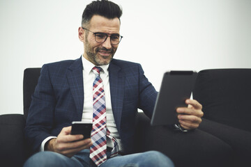 Handsome mature male executive manager in formal wear testing work of innovative software for digital devices updating application on smartphone and touch pad using wifi connection in coworking office