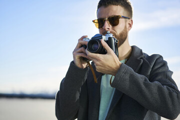 Pensive male photographer thinking about photo composition standing outdoors on advertising area with vintage camera, handsome hipster guy taking picture of urban settings enjoying leisure time