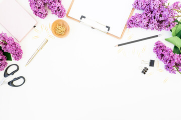 Blogger or freelance workspace with clipboard, notebook, scissors, lilac and accessories on white background. Flat lay, top view. Beauty concept.