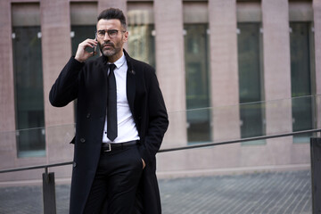 Attractive fashionable dressed businessman left office building to talk on modern mobile phone on street. Handsome mature man 40 years old hearing important information via speed mobile connectivity