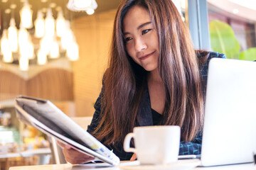 A business woman reading newspaper and drinking coffee in the morning in cafe