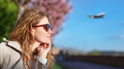 Young redhead woman tourist looking away outdoor at spring, aircraft in the air