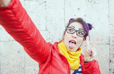 Fashion hipster woman with colorful hair taking selfie