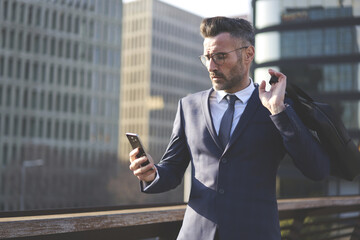 Concentrated matured businessman dressed in formal elegant suit checking email box texting feedback and monitoring latest economic news via application on modern smartphone connected to 4G internet.