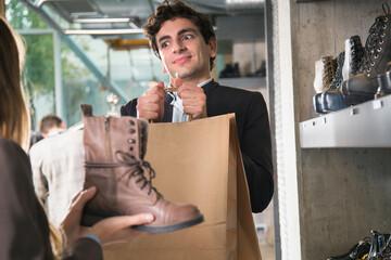 Young man tired of shoe shopping