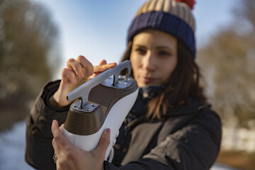 Woman examining the blade of her ice skate