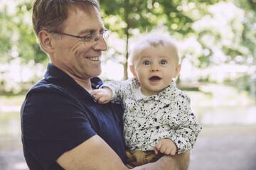 Smiling father holding amazed baby boy outdoors