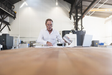 Man with plan, product and laptop on table in factory