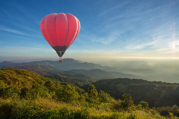 Foto op Plexiglas Ballon Colorful hot air balloon over the mountain at sunset