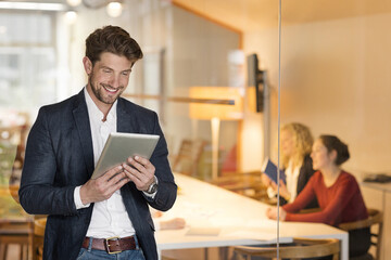 Young businessman in office using digital tablet, with coworkers in background