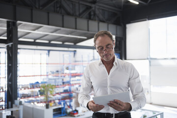 Man with tablet on factory shop floor
