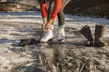 Close-up of woman putting on ice skates on canal