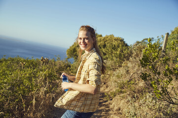 South Africa, Cape Town, Signal Hill, smiling young woman hiking at the coast
