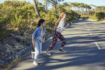 South Africa, Cape Town, Signal Hill, two happy young women crossing country road