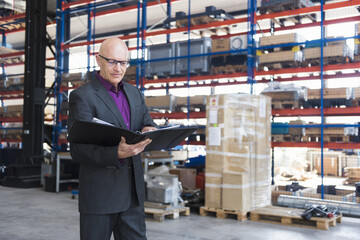 Businessman with documents on factory shop floor