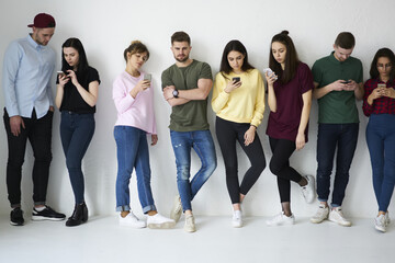 Young male and female hipsters addicted to online communication modern technology preferring sending SMS on smartphone instead of real conversation with friends,students blogging in social networks