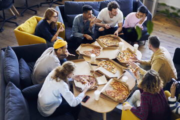 Group of male and female coworkers having  lunch break eating pizza together in office, overhead shot of young casually dressed staff members recreating after finishing tasks making fast snack .