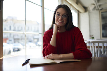 Half length portrait of cheerful attractive woman in eyeglasses looking at the camera while spending leisure time sitting in cafe,smiling creative student of university organizing study process