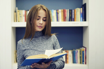 Intelligent good looking female reader searching interesting literature for reading in free time standing indoors in university library interior while enjoying bestseller of young talented author