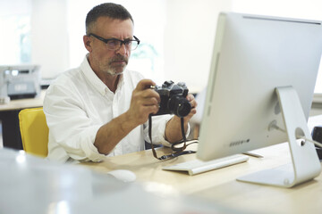 Serious concentrated mature photographer in optical eye making photo of modern computer while testing new vintage film camera sitting in spacious coworking space. Photo amateur analysing new device