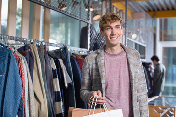 Happy young man with his shopping bags