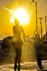 Beautiful silhouette of fit female showering outdoors on beach at sunset