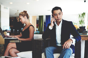 Handsome businessman with serious face discussing work issues by mobile phone, young smart woman working on laptop computer, successful male and female entrepreneurs sitting in modern office interior