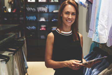 Portrait of a young businesswoman with beautiful smile holding digital tablet while standing in her fashion boutique, gorgeous female owner using touch pad for job in trendy shop during work day