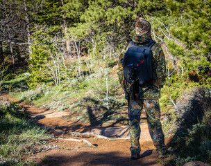 Hiker man photographer in camouflage outfit with a backpack and tripod standing on a mountain forest trail and watching wildlife, rear view